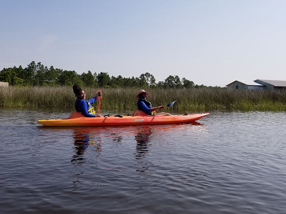 Two students kayaking and looking at the camera