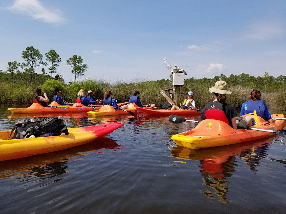 Students in kayaks listening to an instructor speak