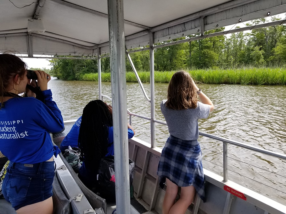 Three students on a boat look into the distance with binoculars